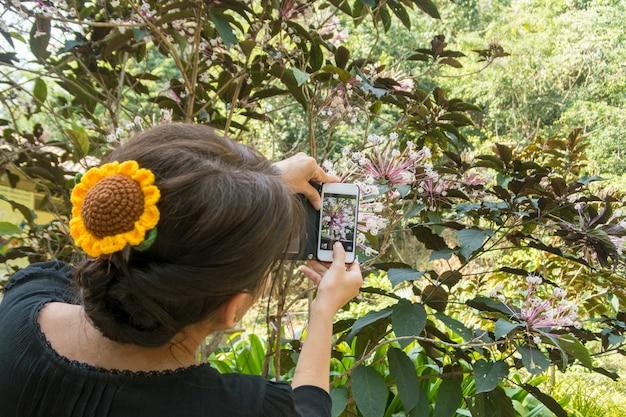 Mulher asiática que tira fotos de flores.