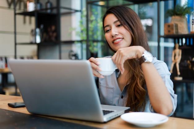Mulher asiática que trabalha e bebe café no café com sorriso de computador portátil e trabalho feliz