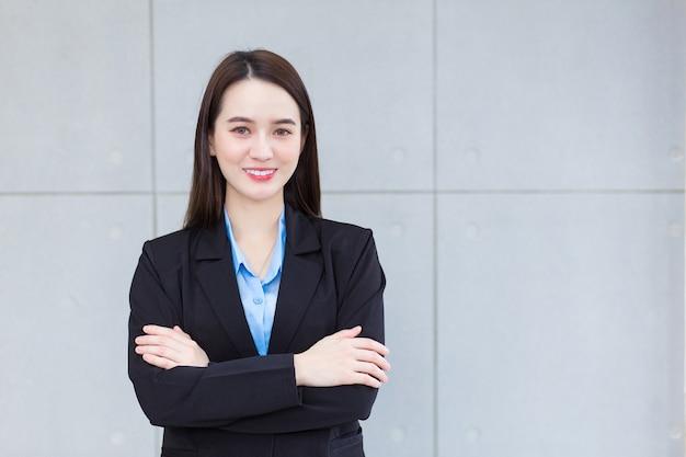 Mulher asiática que trabalha e tem cabelo comprido, usa um terno formal preto com camisa azul que cruza os braços