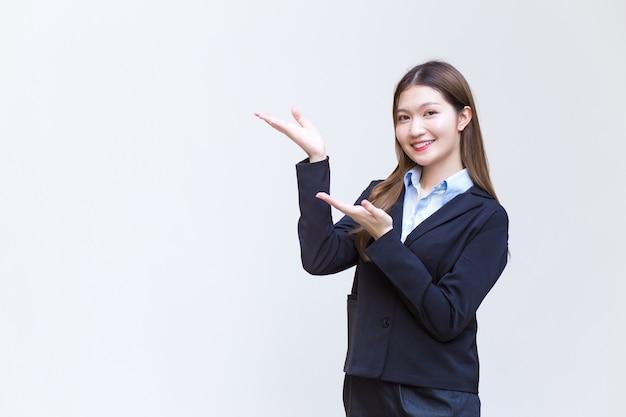 Mulher asiática que trabalha e tem cabelo comprido, usa um terno formal preto com camisa azul
