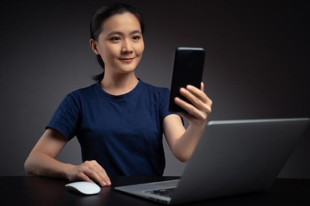 Mulher asiática que trabalha no laptop faz a varredura de rosto por smartphone usando o sistema de reconhecimento facial.