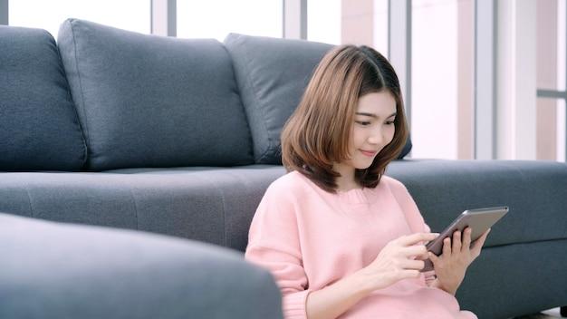 Mulher asiática que usa a tabuleta ao encontrar-se no sofá home em sua sala de visitas.