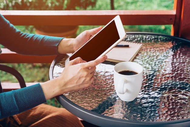 Mulher asiática que usa o comprimido na mesa e o café no jardim com o vintage tonificado.