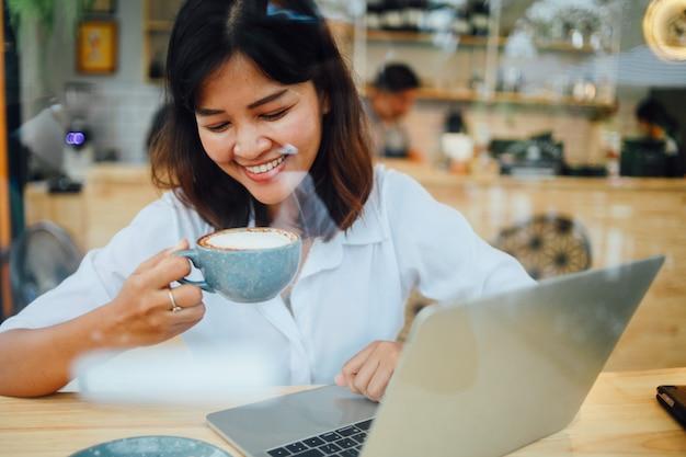 Mulher asiática que usa o laptop no café da cafetaria