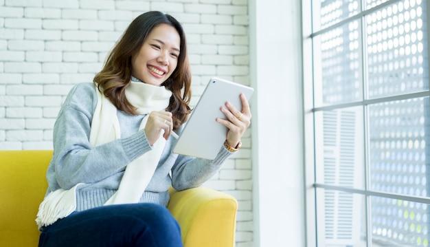 Mulher asiática que usa o portátil da tabuleta em casa, conceito dos povos do estilo de vida