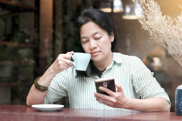 Mulher asiática que usa o telefone inteligente e que bebe café enquanto está sentada ao lado do fundo do café da janela