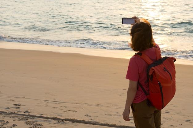 Mulher asiática que usa o telemóvel em férias do curso no oceano.