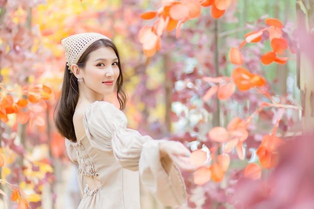 Mulher asiática que usa um vestido marrom claro fica de pé e sorri feliz com a floresta de laranja (folha laranja).
