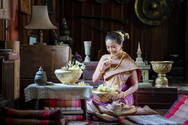Mulher asiática que veste a cultura tradicional de laos, menina bonita de laos no traje de laos no templo, estilo do vintage, luang prabang, laos.