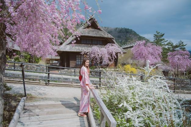 Mulher asiática que veste o quimono japonês tradicional com a flor de cerejeira no japão.