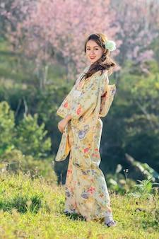 Mulher asiática que veste o quimono tradicional japonês no jardim de sakura.