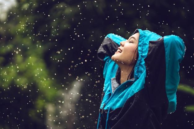 Mulher asiática que veste uma capa de chuva fora. ela está feliz.