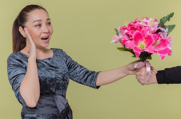 Mulher asiática recebendo buquê de flores, parecendo surpresa e feliz, comemorando o dia internacional da mulher em pé sobre a parede verde