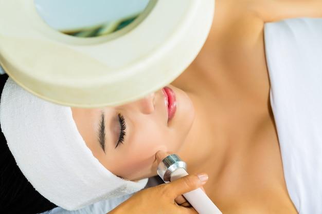 Mulher asiática, recebendo um tratamento facial no spa
