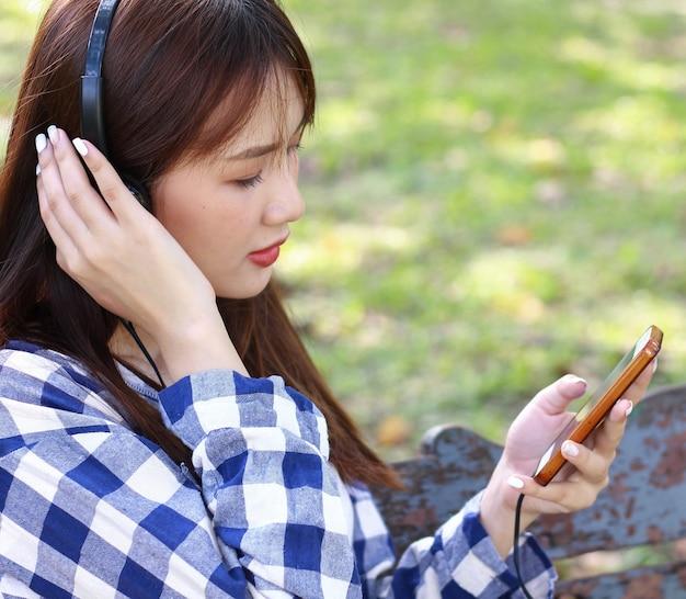 Mulher asiática relaxa ouvindo música em smartphones alegremente no parque.