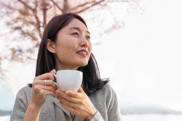 Mulher asiática relaxando ao ar livre ao lado de uma cerejeira
