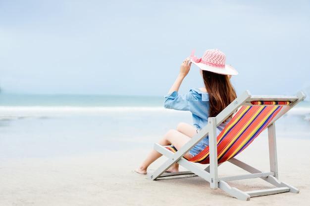 Mulher asiática relaxando em uma cadeira de praia e levantando os braços para pegar um chapéu