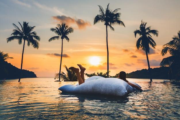 Mulher asiática relaxar na piscina na praia por do sol na tailândia
