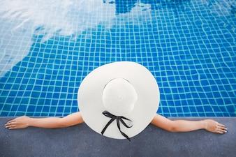 Mulher asiática relaxar na piscina na praia