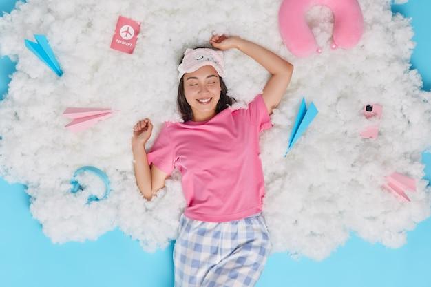 Mulher asiática revigorada acordando de manhã esticando os braços e se sentindo feliz