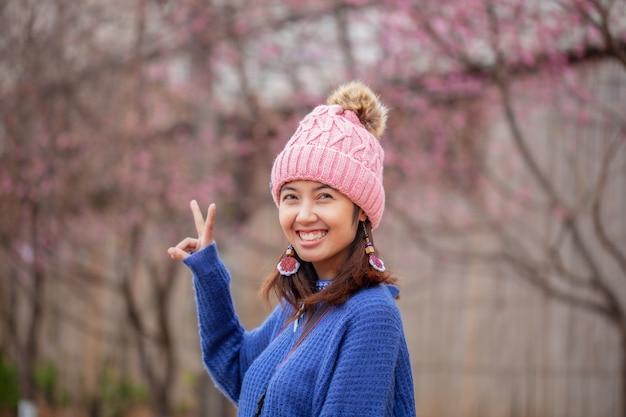 Mulher asiática rostos sorridentes felizes usando chapéus e suéteres, com mãos de cinco centímetros. Foto Premium