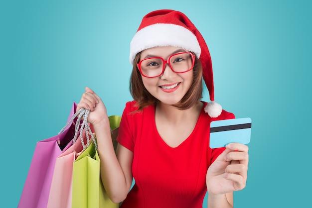 Mulher asiática santa segurando sacolas de compras e cartão de crédito contra a vinheta azul