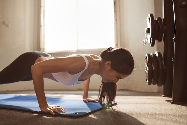 Mulher asiática são flexões no ginásio