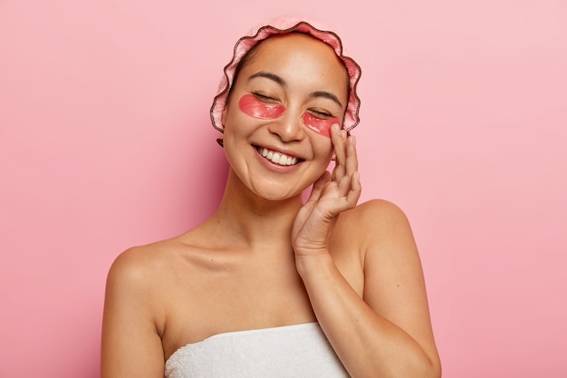 Mulher asiática satisfeita aplica adesivos de colágeno para reduzir o inchaço, sorri positivamente, mostra dentes brancos, usa touca de banho macia, fica enrolada em toalha, faz procedimentos de beleza antes do encontro com o namorado