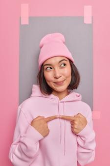 Mulher asiática satisfeita com uma expressão sonhadora pensa em algo gesticula com o dedo indicador desvia o olhar vestida em poses de moletom confortáveis contra a parede vazia do estúdio