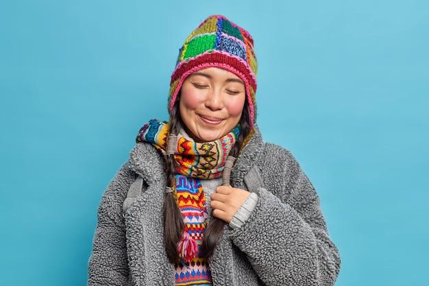 Mulher asiática satisfeita e satisfeita fecha os olhos e sorri agradavelmente usando chapéu de tricô e cachecol casaco quente para o inverno frio tem duas tranças lembra algo agradável isolado sobre a parede azul