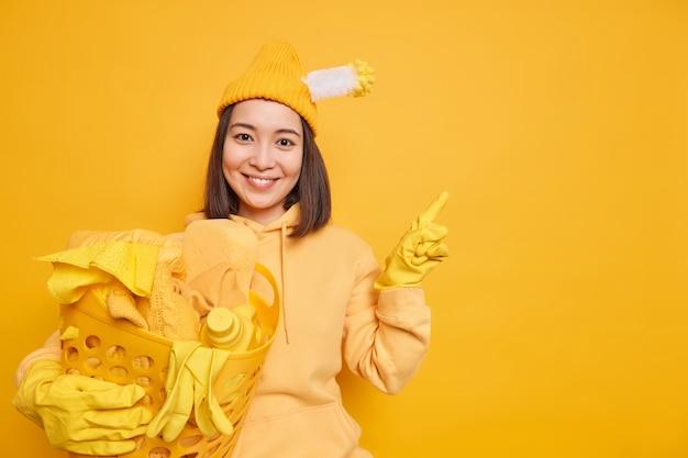 Mulher asiática satisfeita lavando roupa em casa usa chapéu com escova de banheiro presa com capuz e luvas de borracha apontadas para longe no espaço de cópia em branco isolado sobre fundo amarelo mostra produto para limpeza