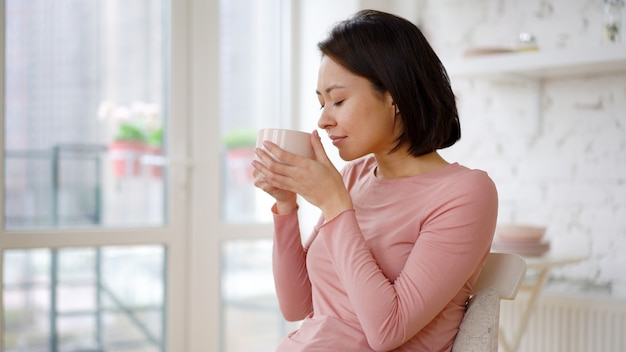 Mulher asiática satisfeita multiétnica desfrutando de uma xícara de café ou chá bebendo uma bebida quente em casa