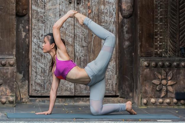 Mulher asiática saudável da ioga que faz o pose da ioga em casa.