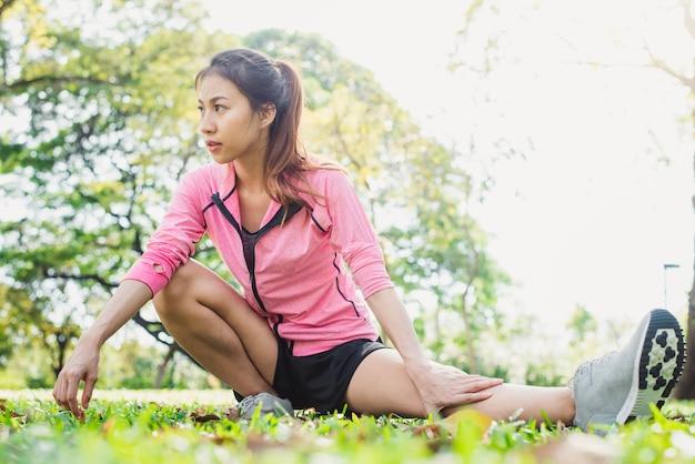 Mulher asiática saudável que se exercita no parque. ajustar jovem fazendo treino de treino pela manhã