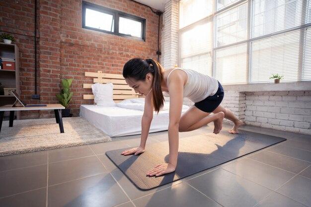 Mulher asiática se exercita em casa, ela é representada como