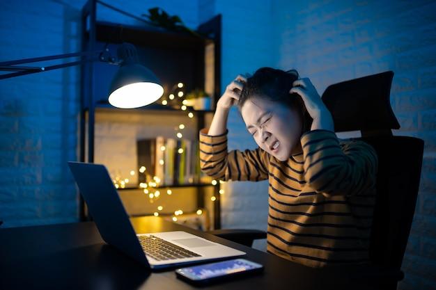 Mulher asiática se sente confusa coçando a cabeça e trabalhando em um laptop horas extras em casa. . trabalhe em casa para evitar o conceito covid 19 do coronavírus.