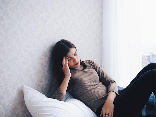 Mulher asiática se sente mal, ela deitada no sofá