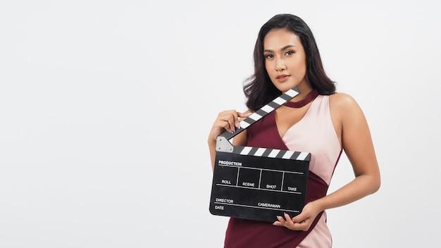 Mulher asiática segura claquete preta ou quadro de filme isolado no fundo branco. ela tem pele bronzeada, filme de programa, filmes ou conceito de produção de cinema.
