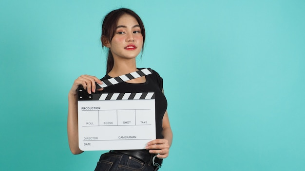 Mulher asiática segurando claquete ou filme ardósia branca sobre fundo verde menta ou azul tiffany.