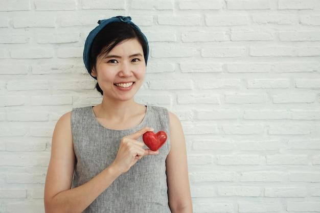 Mulher asiática segurando coração vermelho, seguro de saúde, conceito de caridade doação, dia mundial do coração