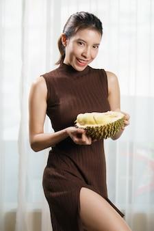 Mulher asiática segurando durian em casa.