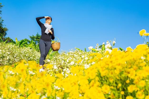 Mulher asiática segurando flores de crisântemos e olhando para a frente no jardim florido