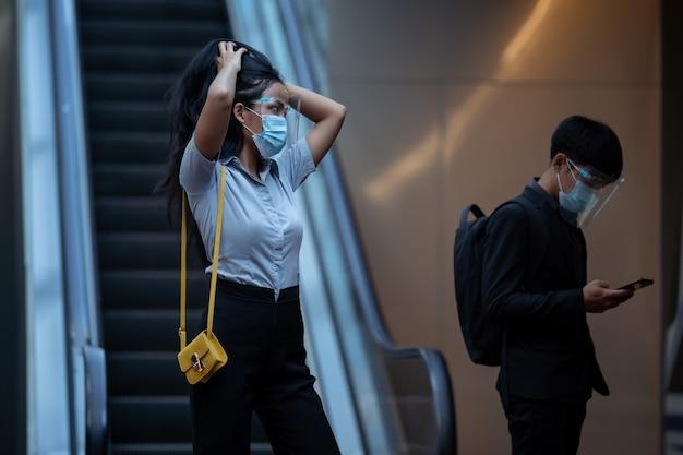 Mulher asiática, segurando o cabelo ela usa uma máscara para se proteger contra o vírus.