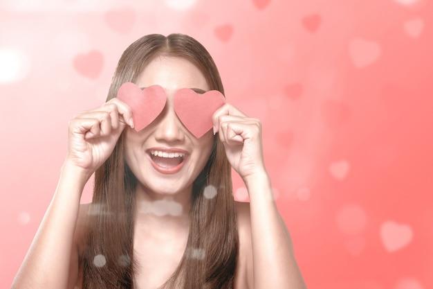 Mulher asiática, segurando o coração vermelho