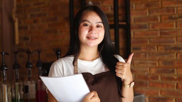 Mulher asiática segurando o menu e escrevendo o pedido