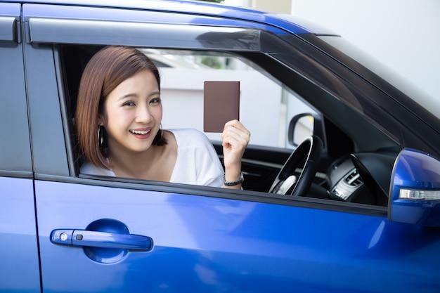 Mulher asiática, segurando o passaporte, sentado no banco do motorista no carro