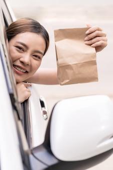 Mulher asiática, segurando o saco de comida da unidade através do restaurante de serviço