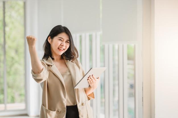 Mulher asiática, segurando o tablet digital e levantando o braço