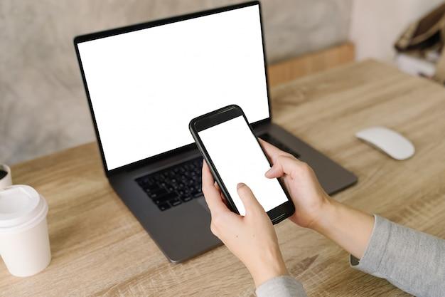 Mulher asiática, segurando o telefone e usando o computador portátil na mesa de madeira