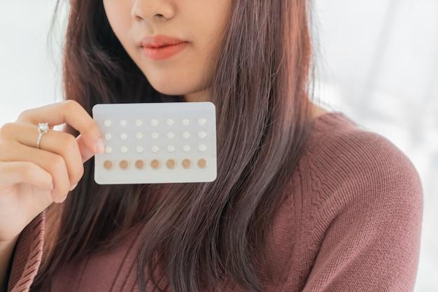 Mulher asiática, segurando, pílula anticoncepcional